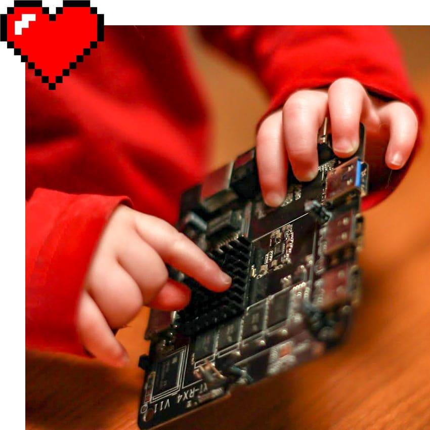 Babyhände spielen und zeigen auf Einplatinencomputer